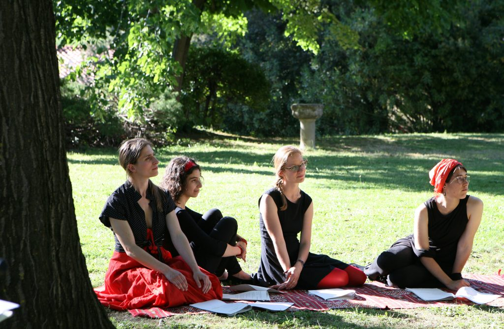 Women wearing red and black sit on grass in the sunshine
